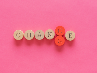 Photo of wooden pegs spelling change/chance with pink background and text